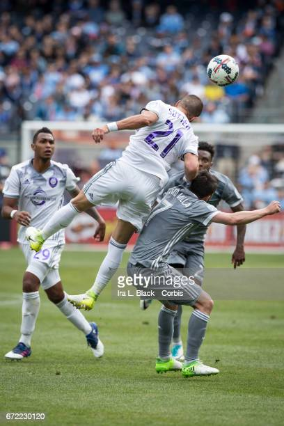 Forward and Captain David Villa of New York City FC hunches over which Scott Sutter of Orlando City SC jumps over him to head the ball during the MLS...