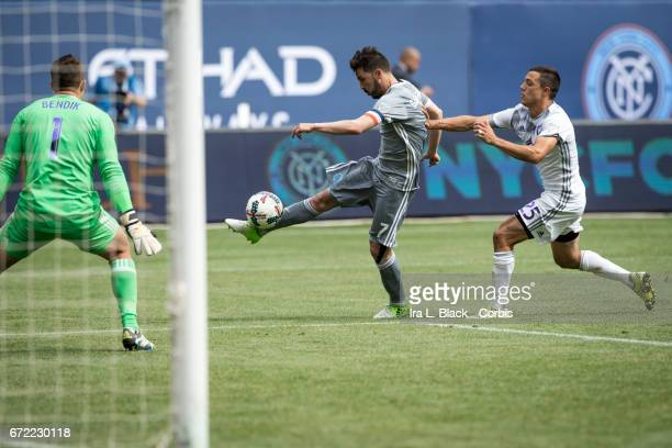 Forward and Captain David Villa of New York City FC kicks the ball for the goal after getting past Donny Toia of Orlando City SC during the MLS match...