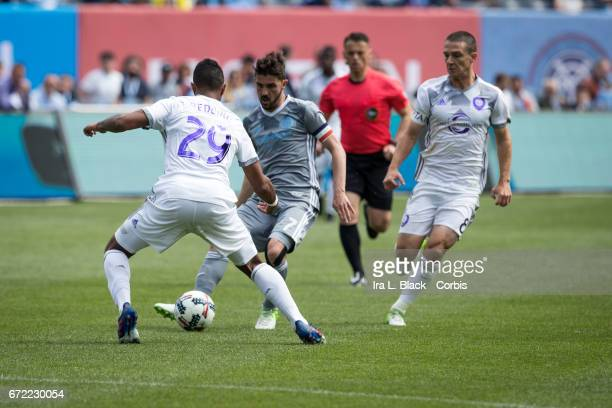 Forward and Captain David Villa of New York City FC passes the ball through the legs of Tommy Redding of Orlando City SC during the MLS match between...