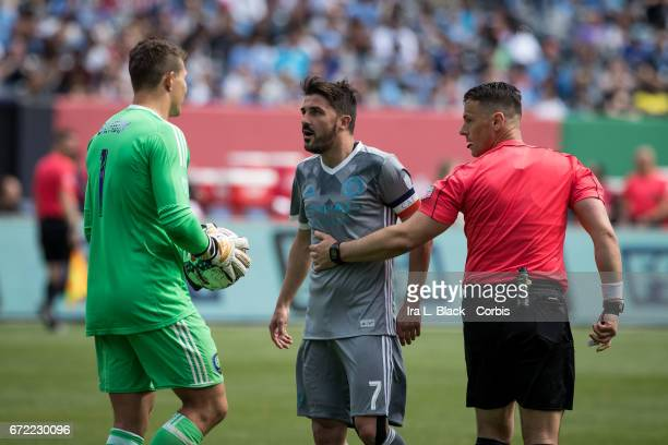 Forward and Captain David Villa of New York City FC starts to have words with Joe Bendik of Orlando City SC after getting a yellow card during the...