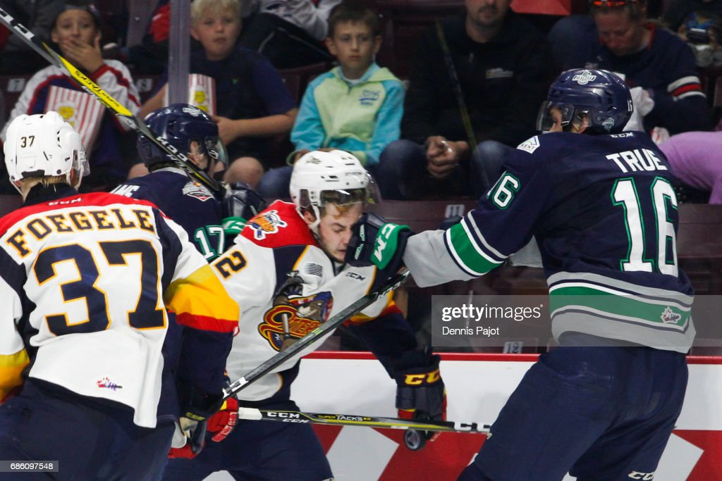 Forward Anthony Cirelli #22 of the Erie Otters receives a glove to the face from forward Alexander True #16 of the Seattle Thunderbirds on May 20, 2017 during Game 2 of the Mastercard Memorial Cup at the WFCU Centre in Windsor, Ontario, Canada.