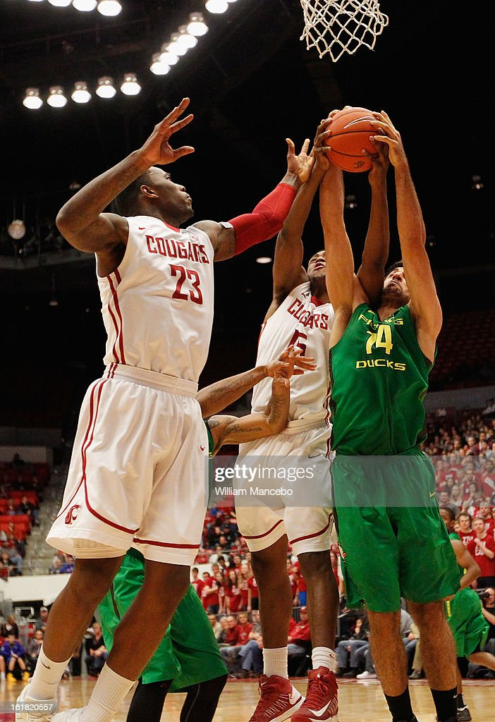 Forward Arsalan Kazemi #14 of the Oregon Ducks attempts to grab an offensive rebound against D.J. Shelton #23 and Junior Longrus #15 of the Washington State Cougars during the game at Beasley Coliseum on February 16, 2013 in Pullman, Washington.