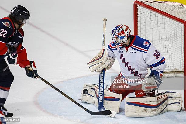 Forward Brendan Lemieux of the Windsor Spitfires slips the puck past goaltender Dawson Carty of the Kitchener Rangers during game 4 of the Western...