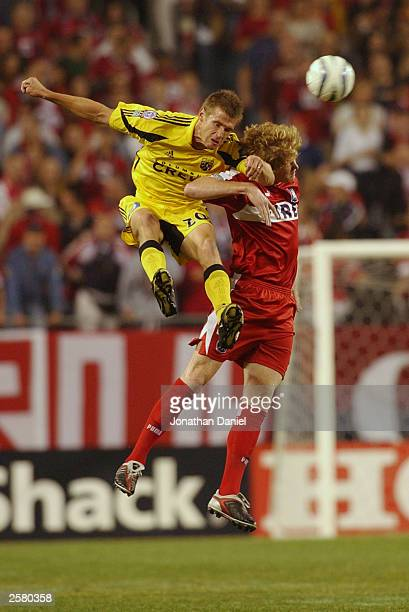 Forward Brian McBride of the Columbus Crew battles with defender Jim Curtin of the Chicago Fire for a header during a game on October 10 2003 at...