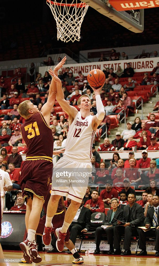 Forward Brock Motum #12 of the Washington State Cougars attempts to shoot a goal against forward Jonathan Gilling #31 of the Arizona State Sun Devils during the second half of the game at Beasley Coliseum on January 31, 2013 in Pullman, Washington.