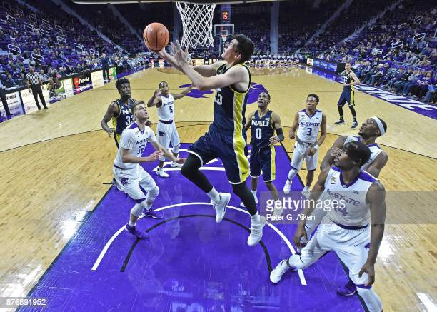 Forward Brooks Debisschop of the Northern Arizona Lumberjacks drives to the basket between defenders Makol Mawien and Dean Wade of the Kansas State...