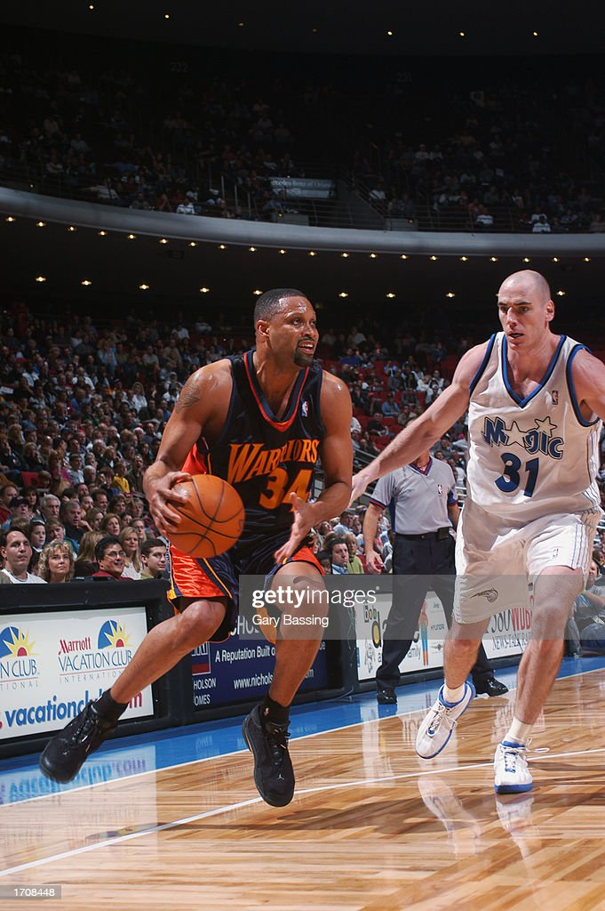 Forward Chris Mills #34 of the Golden State Warriors dribbles past center Pat Burke #31 of the Orlando Magic during the game at TD Waterhouse Centre on December 13, 2002 in Orlando, Florida. The Magic won 111-85.