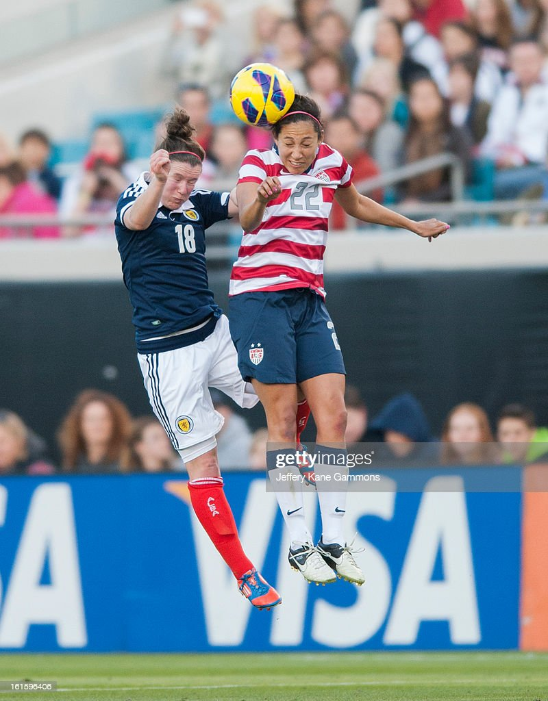 Forward Christen Press #22 of the United States heads the ball against Forward Emma Mitchell #18 of Scotland during the game at EverBank Field on February 9, 2013 in Jacksonville, Florida.