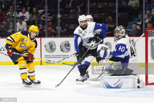 Forward Christian Girhiny of the Erie Otters battles for a rebound against goaltender Callum Booth of the Saint John Sea Dogs on May 26 2017 during...