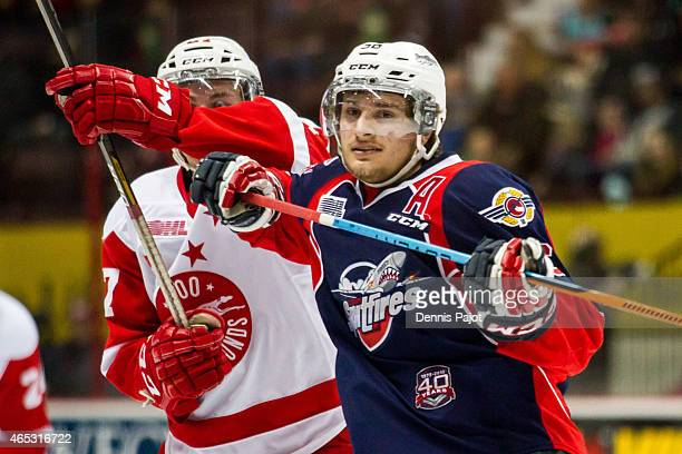 Forward Cristiano DiGiacinto of the Windsor Spitfires battles against forward Michael Bunting of the Sault Ste Marie Greyhounds on March 5 2015 at...