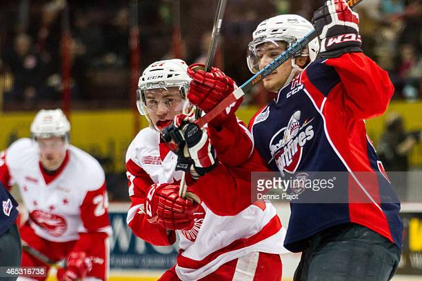 Forward Cristiano DiGiacinto of the Windsor Spitfires battles on a faceoff against forward Michael Bunting of the Sault Ste Marie Greyhounds on March...