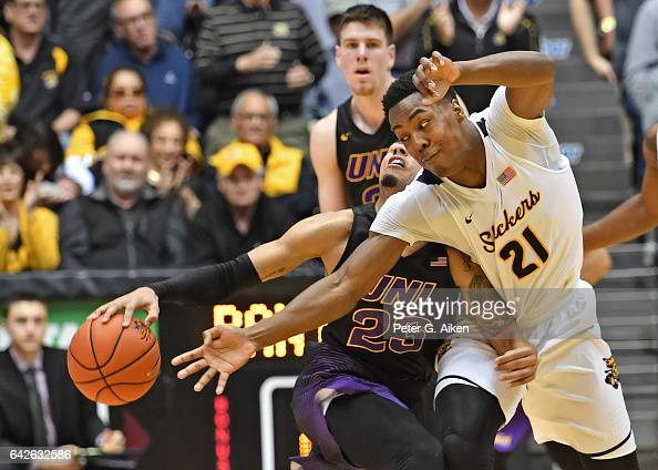Forward Darral Willis Jr #21 of the Wichita State Shockers reaches in for the ball against guard Jordan Ashton of the Northern Iowa Panthers during...