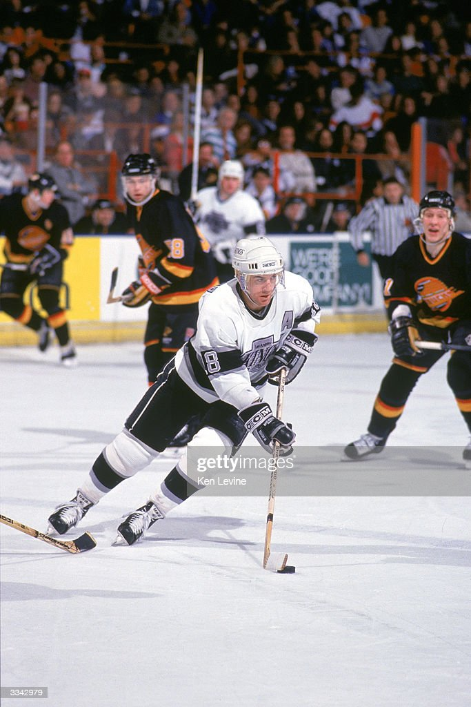 Forward Dave Taylor of the Los Angeles Kings skates with the puck against the Vancouver Canucks during the 199091 season at the Great Western Forum...