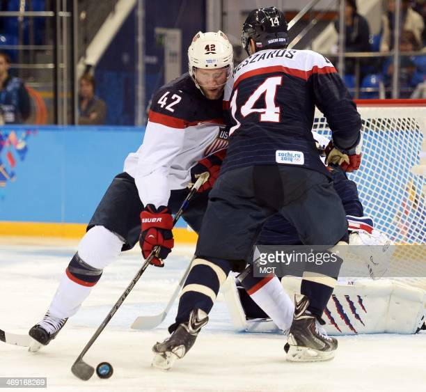 USA forward David Backes tries to gain control of the puck while battling Slovakia defenseman Andrej Meszaros in the second period at Shayba Arena...