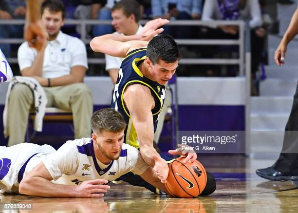 Forward Dean Wade of the Kansas State Wildcats dives for a loose ball on the floor against forward Brooks Debisschop of the Northern Arizona...