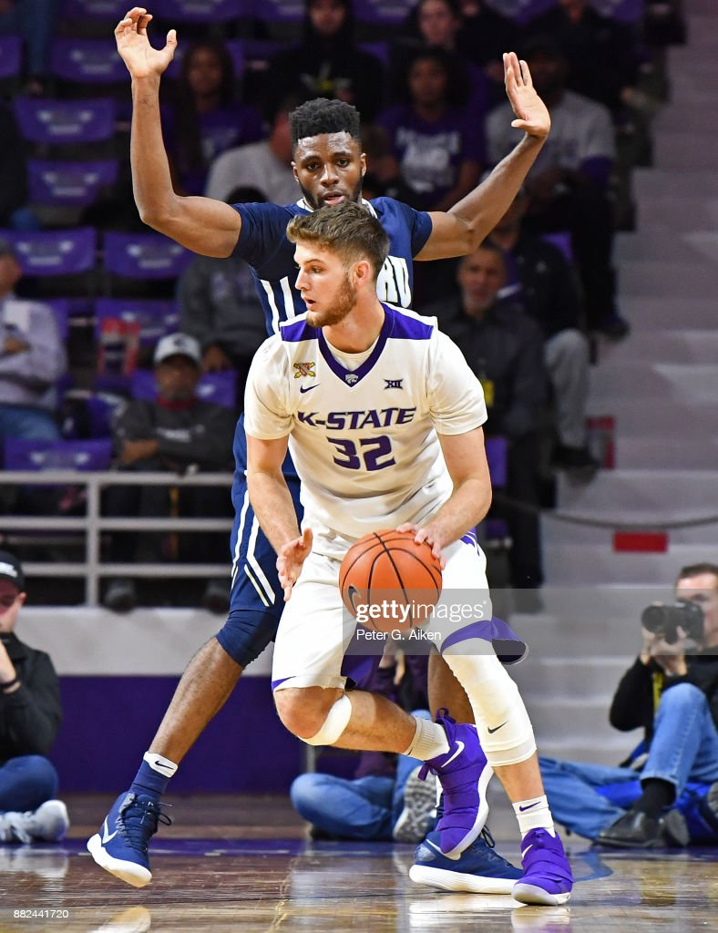 Forward Dean Wade #32 of the Kansas State Wildcats dribble the ball around pressure from forward Chris Miller #52 of the Oral Roberts Golden Eagles during the first half on November 29, 2017 at Bramlage Coliseum in Manhattan, Kansas.
