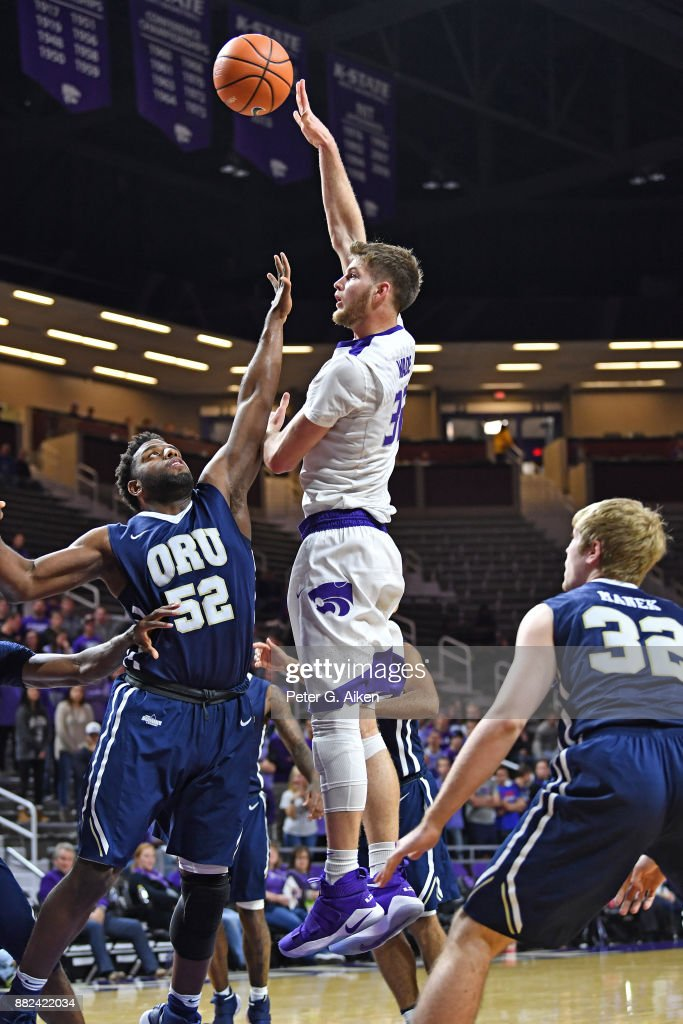 Forward Dean Wade #32 of the Kansas State Wildcats scores a basket over forward Chris Miller #52 of the Oral Roberts Golden Eagles during the second half on November 29, 2017 at Bramlage Coliseum in Manhattan, Kansas.