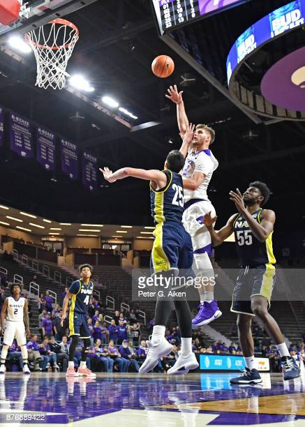 Forward Dean Wade of the Kansas State Wildcats shoots and scores a basket over forward Brooks Debisschop of the Northern Arizona Lumberjacks during...