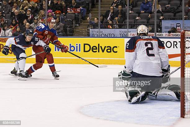 Forward Denis Guryanov of Team Russia shoots on goaltender Matej Tomek of Team Slovakia while fighting off Assistant Captain defenseman Andrej Hatala...