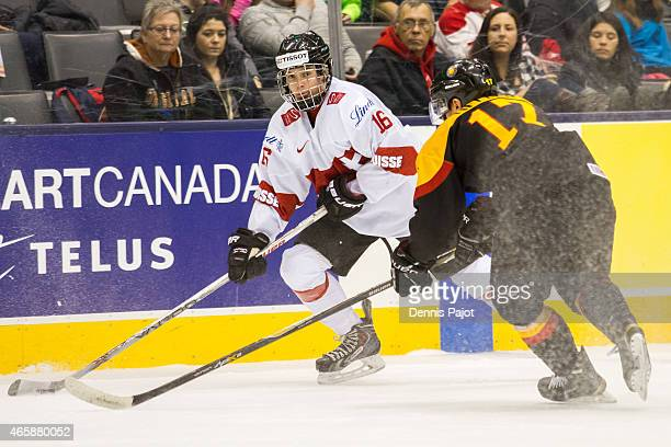Forward Denis Malgin of Switzerland moves the puck against forward Frederik Tiffels of Germany during the 2015 IIHF World Junior Championship on...