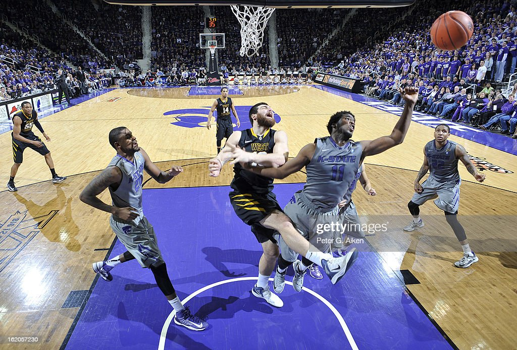 Forward Deniz Kilicli #13 of the West Virginia Mountaineers and guard Nino Williams #11 of the Kansas State Wildcats battle for a rebound during the second half on February 18, 2013 at Bramlage Coliseum in Manhattan, Kansas. Kansas State defeated West Virginia 71-61.