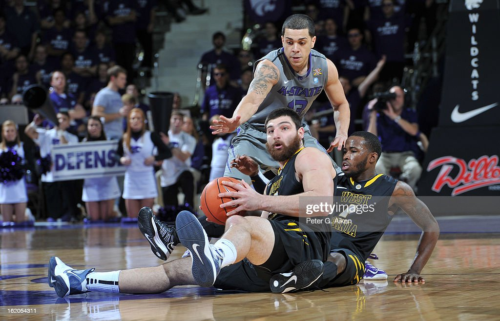 Forward Deniz Kilicli #13 of the West Virginia Mountaineers picks up a loose ball on the floor on top of guard Jabarie Hinds #4, as guard Angel Rodriguez #13 of the Kansas State Wildcats reaches in during the first half on February 18, 2013 at Bramlage Coliseum in Manhattan, Kansas.