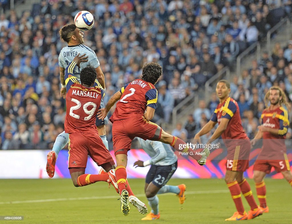 Forward Dominic Dwyer of Sporting Kansas City heads the ball against defenders Kenny Mansally and Tony Beltran of Real Salt Lake during the first...