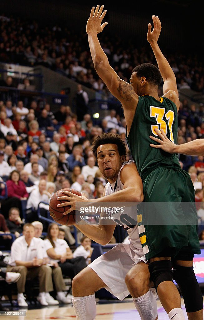 Forward Elias Harris #20 of the Gonzaga Bulldogs drives against forward Frank Rogers # 31 of the San Francisco Dons during the second half of the game at McCarthey Athletic Center on January 26, 2013 in Spokane, Washington.
