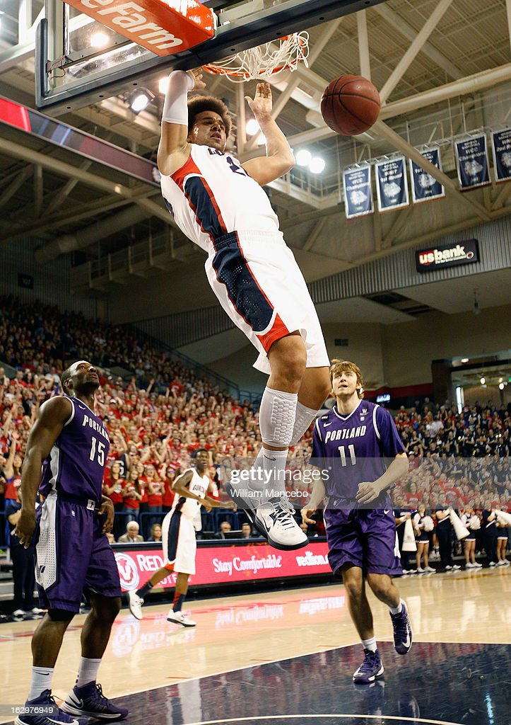 Forward Elias Harris #20 of the Gonzaga Bulldogs dunks while guard Derrick Rodgers #15 and forward Jake Ehlers #11 of the Portland Pilots look on during the first half of the game at McCarthey Athletic Center on March 2, 2013 in Spokane, Washington.