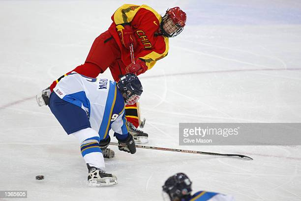 Forward Fengling Jin of China passes the puck as defender Olga Potapova of Kazakhstan tries to block it during their game at the Salt Lake City...
