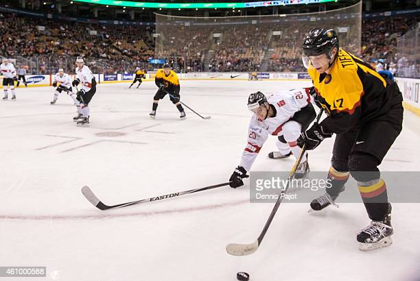Forward Frederik Tiffels of Germany moves the puck against defenceman Simon Kindschi during the 2015 IIHF World Junior Championship on January 03...