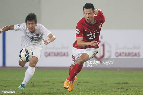 Forward Gao Lin of Guangzhou Evergrande and Yasushi Endo of Kashima Antlers run with the ball during the AFC Asian Champions League match between the...