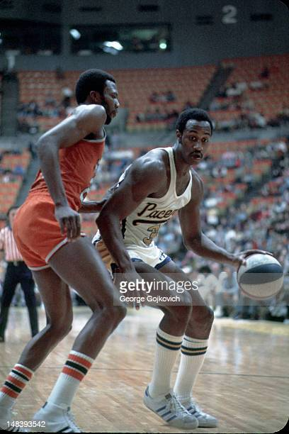 Forward George McGinnis of the Indiana Pacers drives to the basket against forward Marvin Barnes of the Spirits of St Louis during an American...