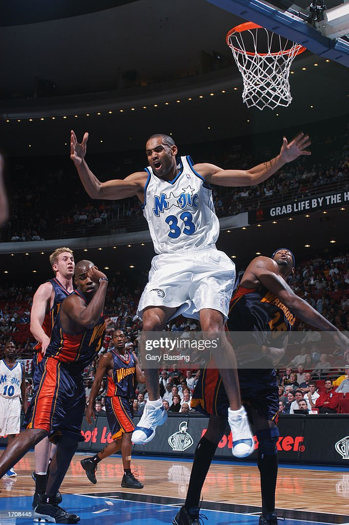 Forward Grant Hill #33 of the Orlando Magic jumps after the shot against center Erick Dampier #25 of the Golden State Warriors during the game at TD Waterhouse Centre on December 13, 2002 in Orlando, Florida. The Magic won 111-85.