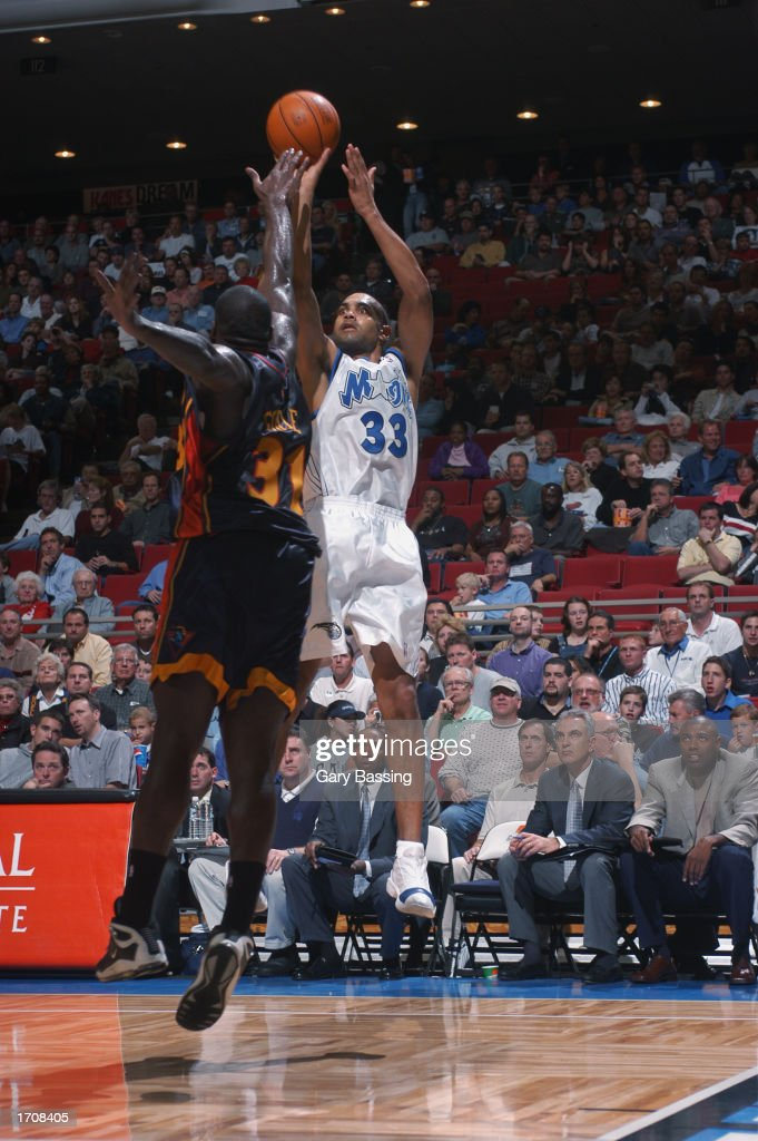 Forward Grant Hill #33 of the Orlando Magic shoots a jump shot over center Adonal Foyle #31 of the Golden State Warriors during the game at TD Waterhouse Centre on December 13, 2002 in Orlando, Florida. The Magic won 111-85.