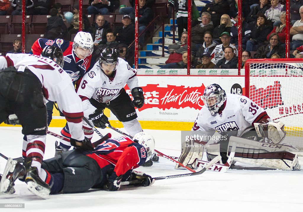 Forward Hayden McCool #27 of the Windsor Spitfires battles for the puck against goaltender Justin Nichols #39 of the Guelph Storm on March 12, 2015 at the WFCU Centre in Windsor, Ontario, Canada.