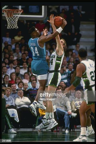 Forward J R Reid of the Charlotte Hornets battles for the ball with center Brad Lohaus of the Milwaukee Bucks during a game at the Bradley Center in...