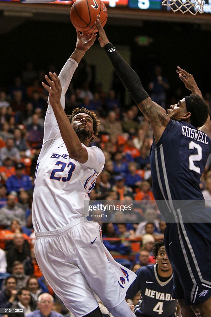 Forward James Webb III of the Boise State Broncos goes up for a shot over the outstretched arms of guard Tyron Criswell of the Nevada Wolf Pack...