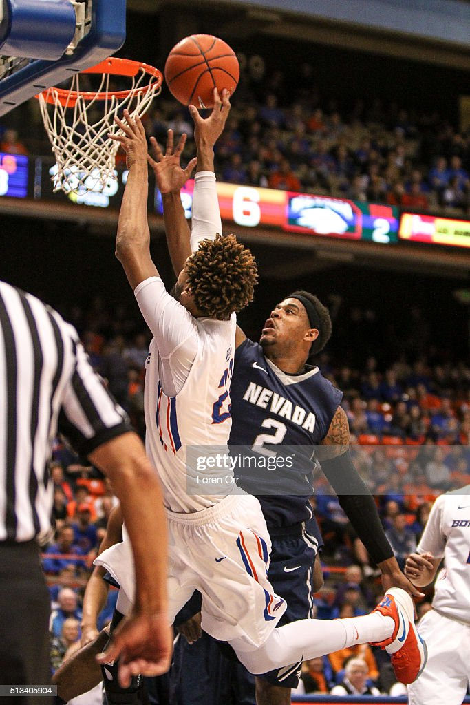 Forward James Webb III of the Boise State Broncos tries to tip a ball into the basket over the defense of guard Tyron Criswell of the Nevada Wolf...