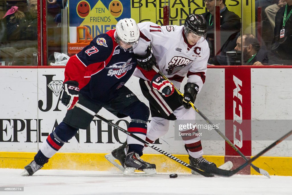 Forward Jason Dickinson #11 of the Guelph Storm battles for the puck against forward Hayden McCool #27 of the Windsor Spitfires on March 12, 2015 at the WFCU Centre in Windsor, Ontario, Canada.