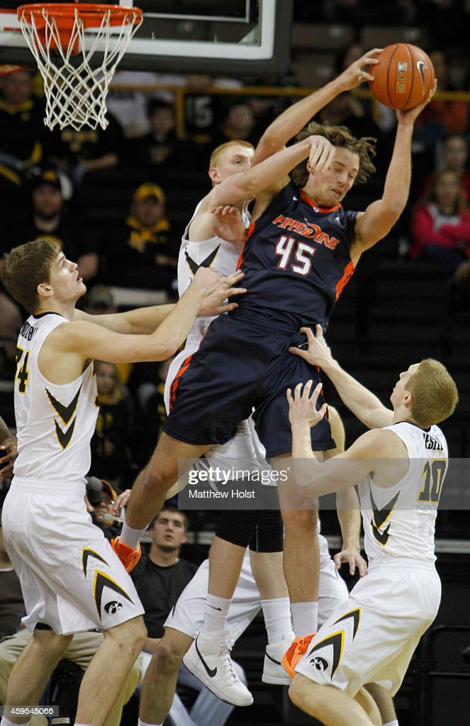 Forward Jett Raines #45 of the Pepperdine Waves grabs a rebound in front of center Adam Woodbury #34, forward <a gi-track='captionPersonalityLinkClicked' href=/galleries/search?phrase=Aaron+White+-+Basketball+Player&family=editorial&specificpeople=14619648 ng-click='$event.stopPropagation()'>Aaron White</a> #30 and guard Mike Gesell #10 of the Iowa Hawkeyes, in the first half on November 24, 2014 at Carver-Hawkeye Arena, in Iowa City, Iowa.