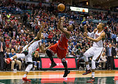 Forward Jimmy Butler of the Chicago Bulls is fouled as he tries to shoot over guard Jerryd Bayless of the Milwaukee Bucks in the second quarter of...