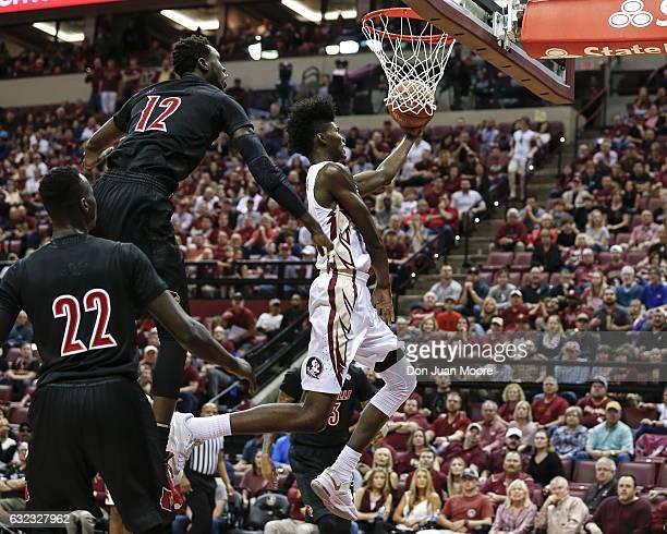 Forward Jonathan Isaac of the Florida State Seminoles drives to the basket against Forwards Adel Deng and Mangok Mathiang of the Louisville Cardinals...