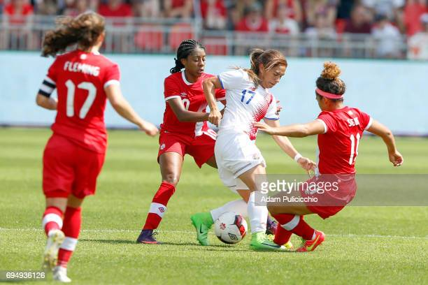 Forward Karla Villaobos of Team Costa Rica tries to hold onto the ball as Midfielder Desiree Scott of Team Canada and her teammate reach in for the...