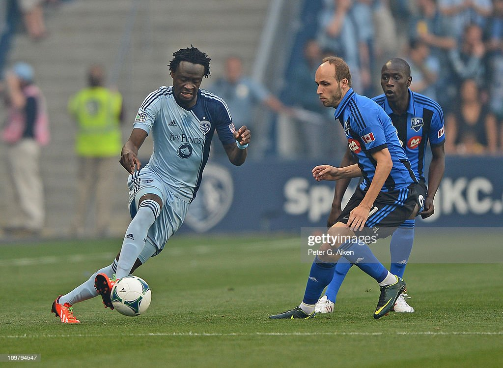 Forward Kei Kamara of Sporting Kansas City makes a play on the ball against midfielder Justin Mapp of the Montreal Impact during the first half on...
