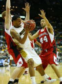 Forward Keith Ramsey of the Missouri Tigers tries to pass the ball while defended by forward Brandon Ubel and guard Ryan Anderson of the Nebraska...