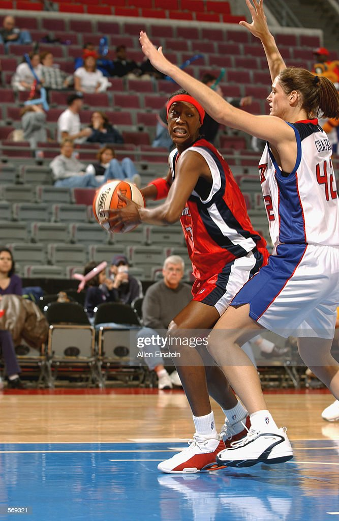 Forward Kelley Gibson #3 of the Houston Comets spins around center Jill Chapman #42 of the Detroit Shock during the preseason WNBA game at the Palace of Auburn Hills in Auburn Hills, Michigan on May 13. 2002. The Comets won 78-62.