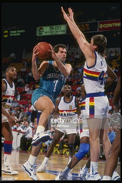 Forward Kelly Tripucka of the Charlotte Hornets tries to drive with the ball as forward Joe Wolf of the Denver Nuggets tries to block during a game...