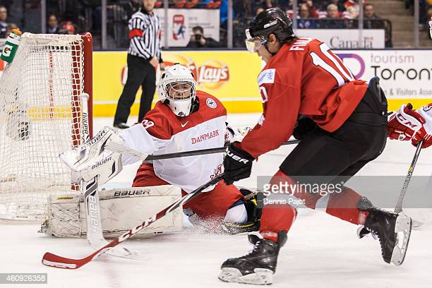 Forward Kevin Fiala of Switzerland moves the puck against goaltender Georg Sorensen of Denmark during the 2015 IIHF World Junior Championship on...