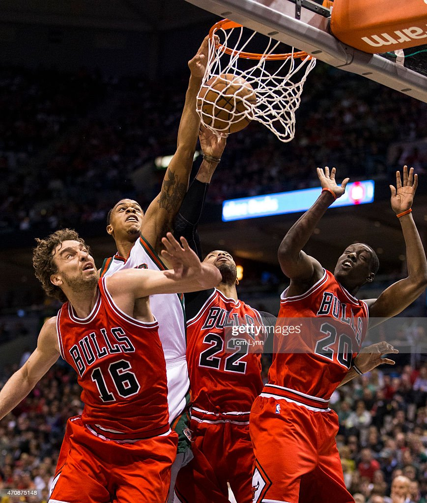 Forward Khris Middleton of the Milwaukee Bucks scores over center Pau Gasol forward Taj Gibson and forward Tony Snell of the Chicago Bulls in the...
